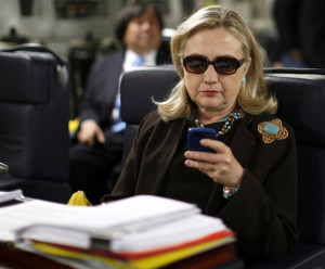 Former Secretary of State Hillary Clinton checks her PDA. REUTERS/Kevin Lamarque